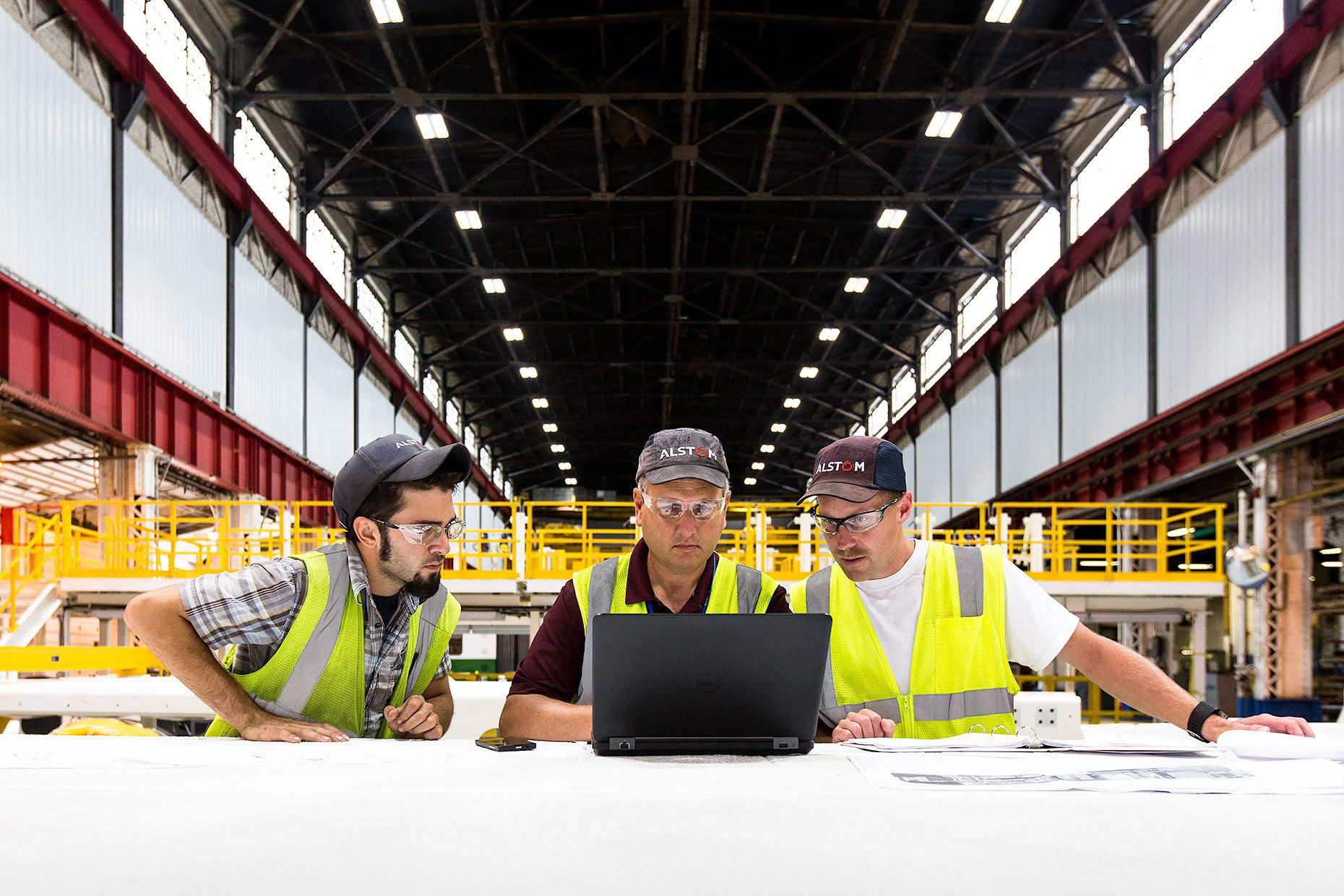 Three train engineers meet around a computer | Scott Gable industrial photographer