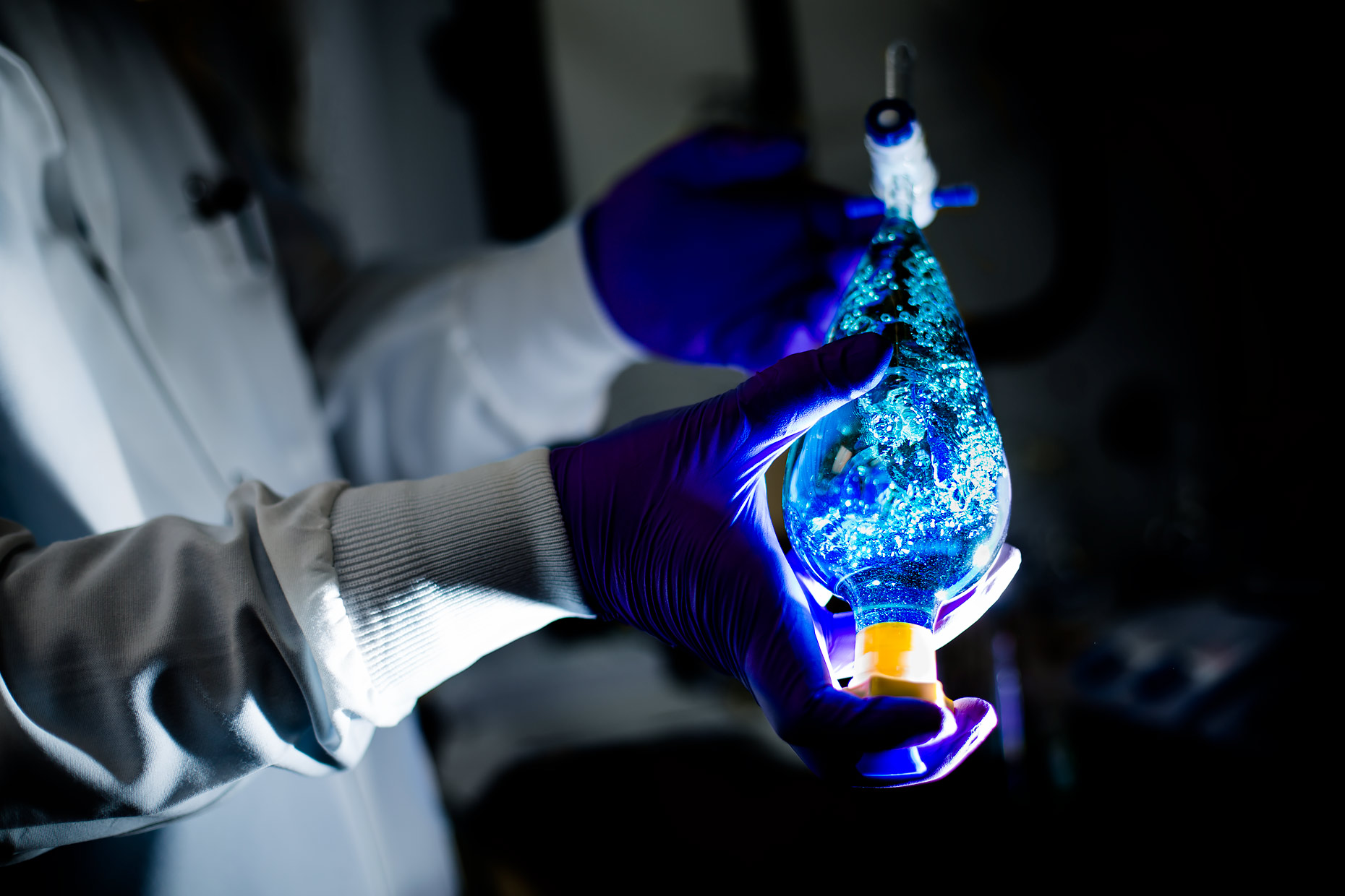 The gloved hands of a technician agitating liquid | Scott Gable industrial photographer