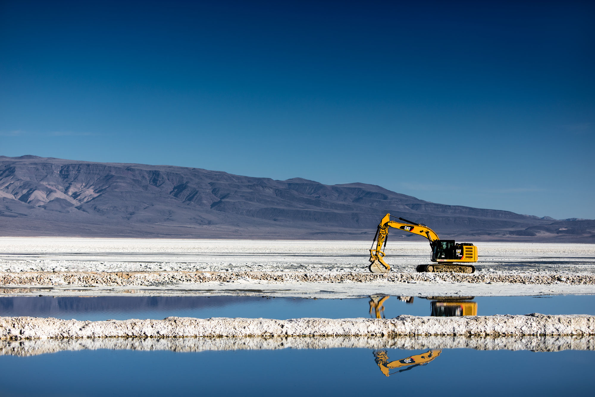 An excavator in the snow with mountains in the background  |  Scott Gable industrial photographer