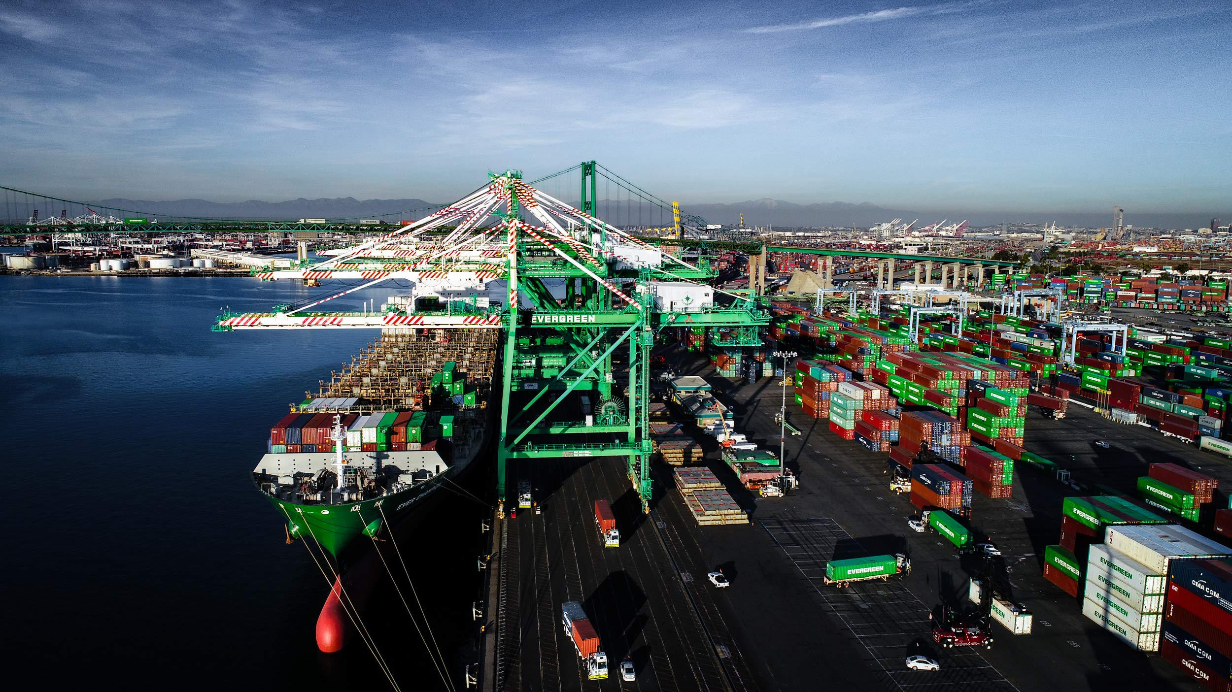 Aerial view of Evergreen crane unloading shipping containers from a ship onto semi trucks in the Port of Long Beach | Scott Gable industrial photographer