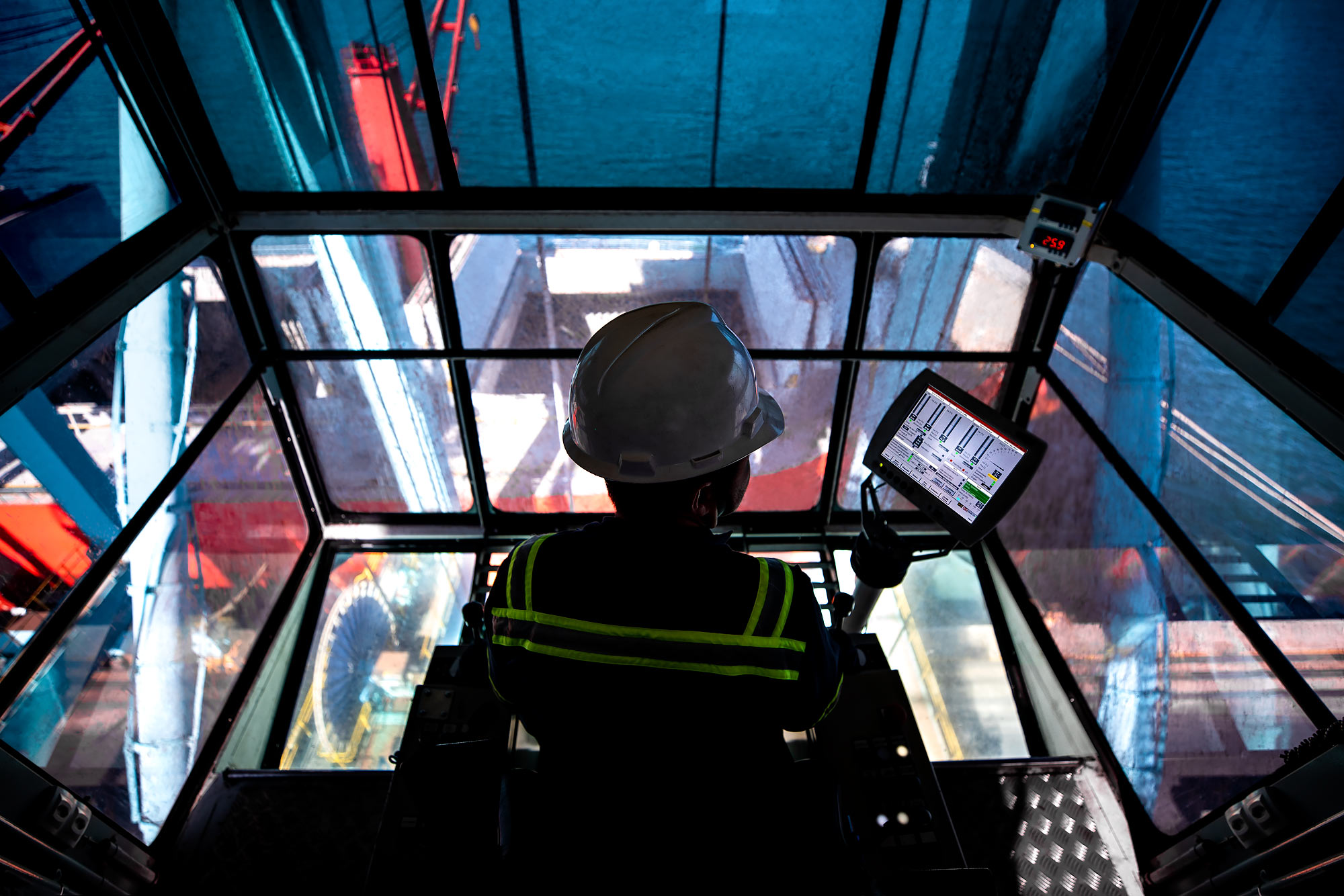 A view from the control booth of an industrial marine crane with technician silhouette |  Scott Gable industrial photographer