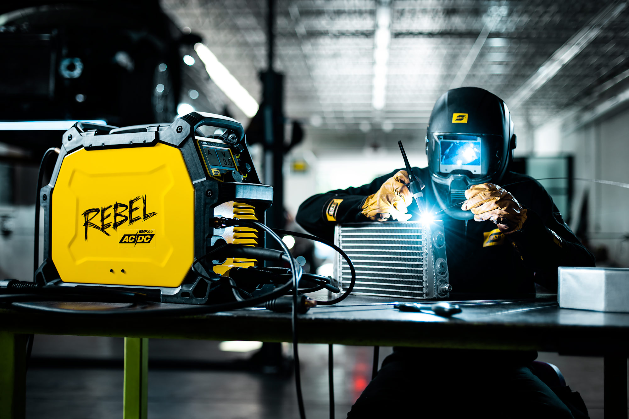 Welder works sitting at bench |  Scott Gable industrial photographer