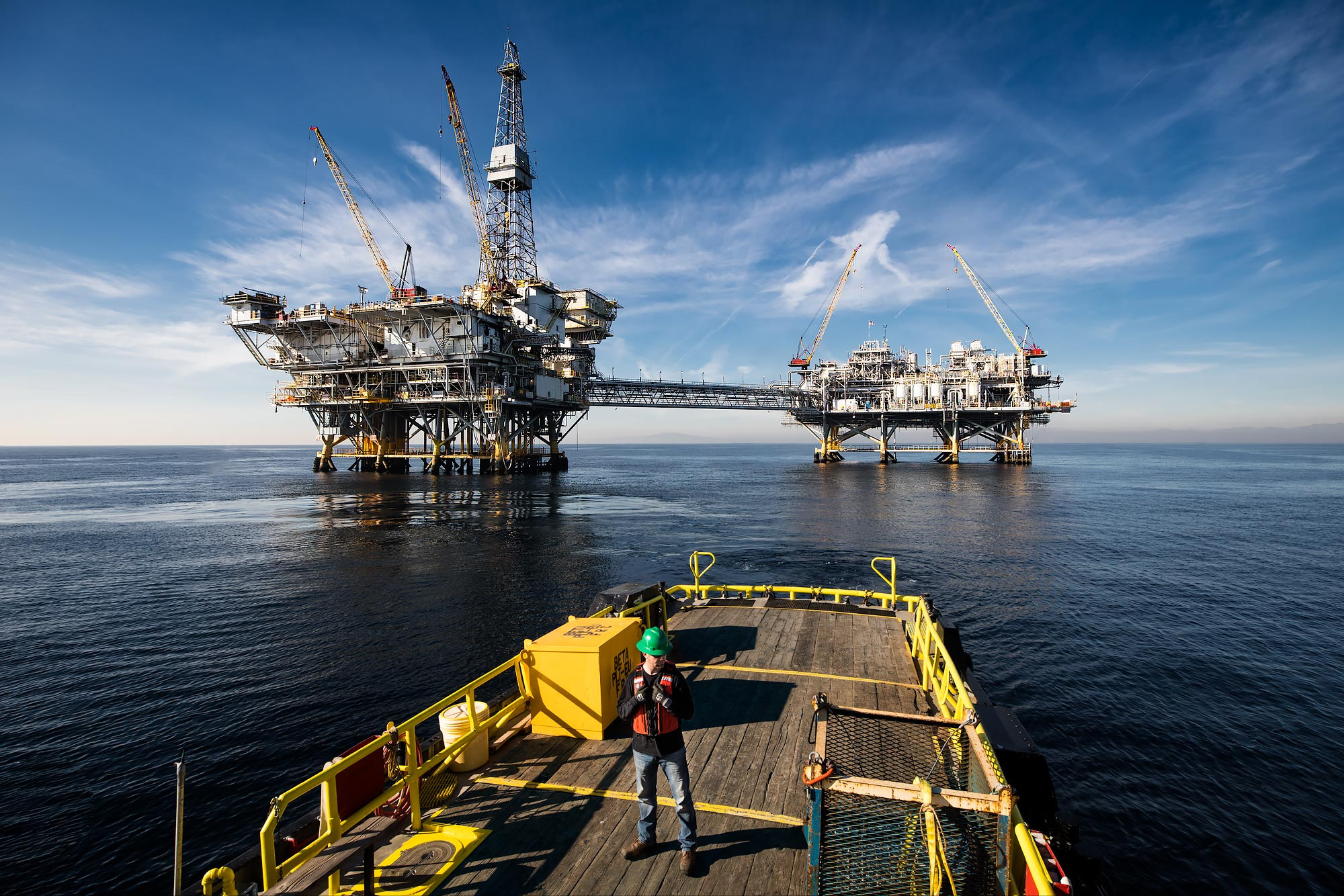 A technician stands on deck with off-shore oil platforms in the background |  Scott Gable industrial photographer