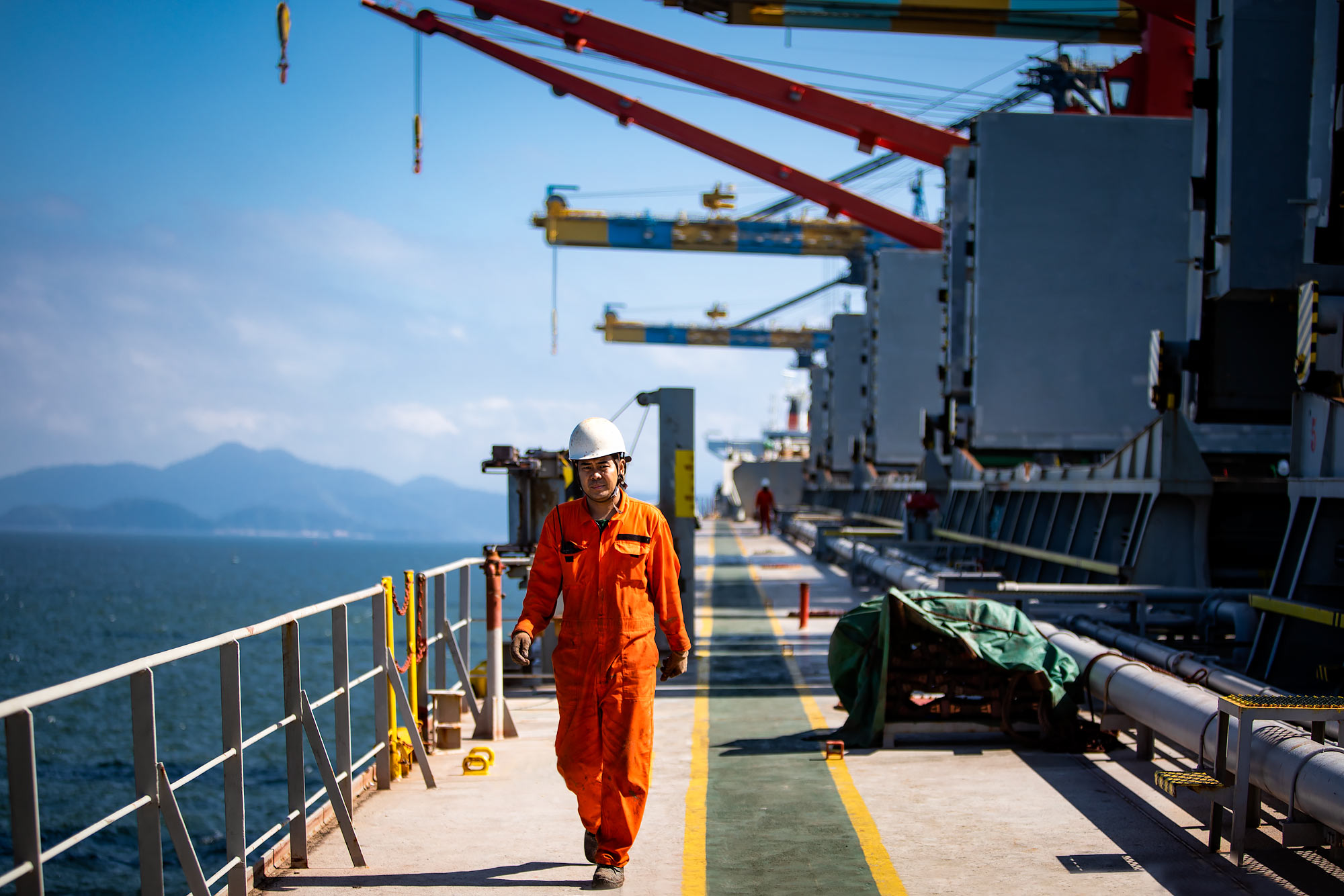 Dockworker walking beneath industrial cargo cranes |  Scott Gable industrial photographer