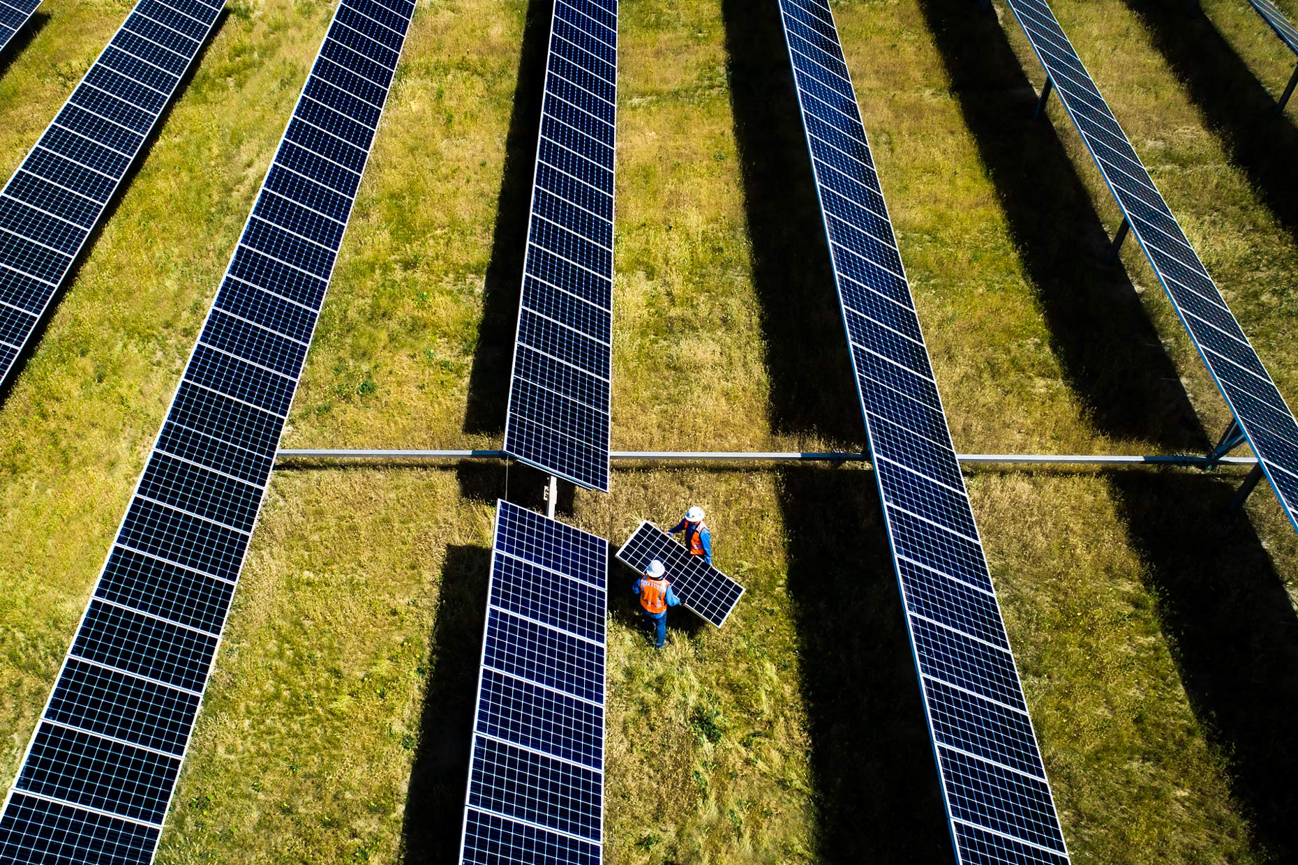 Drone view as two technicians replace a panel in a solar array | Scott Gable industrial photographer
