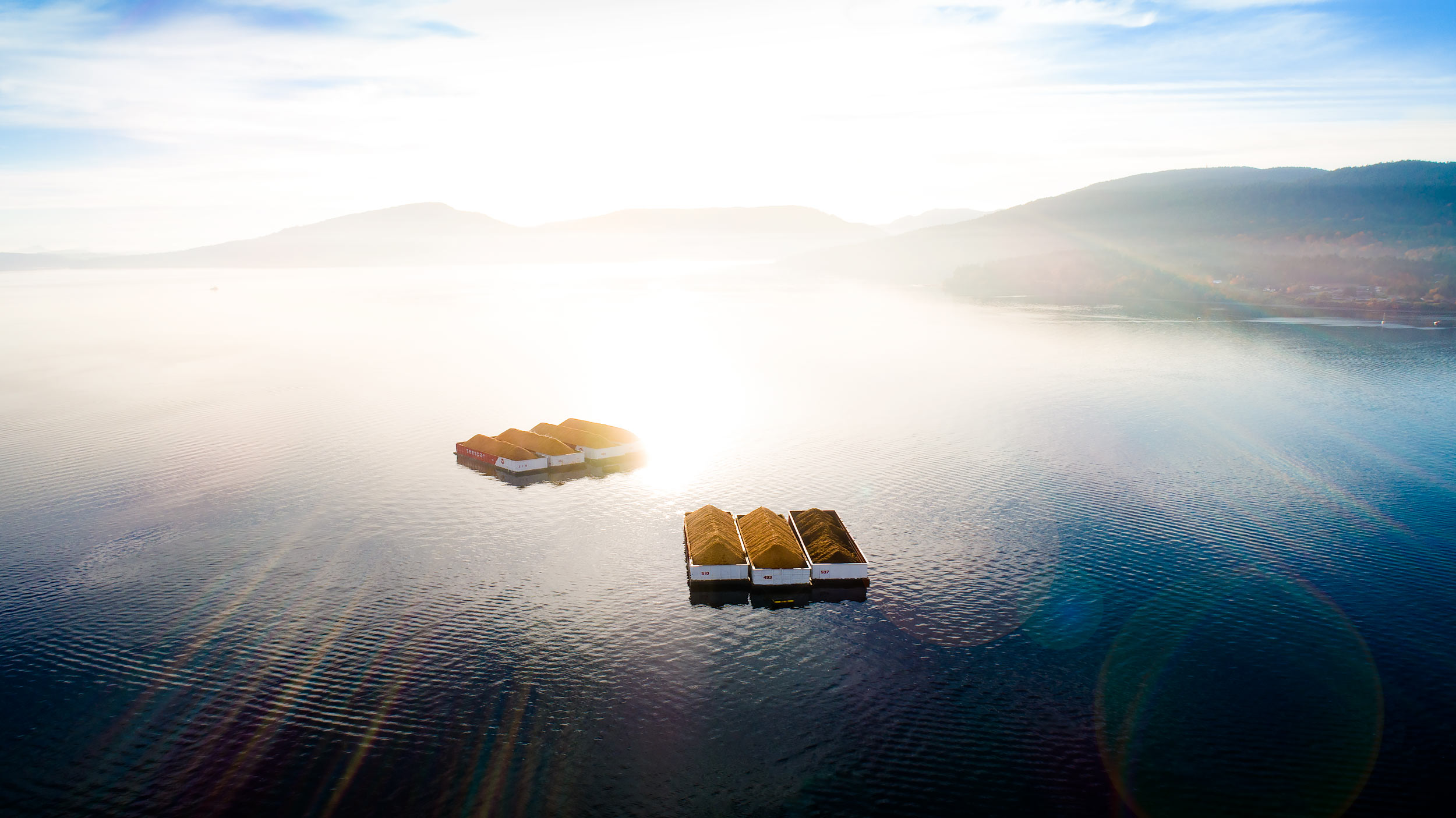 Aerial view of timber barges on shimmering water | Scott Gable industrial photographer