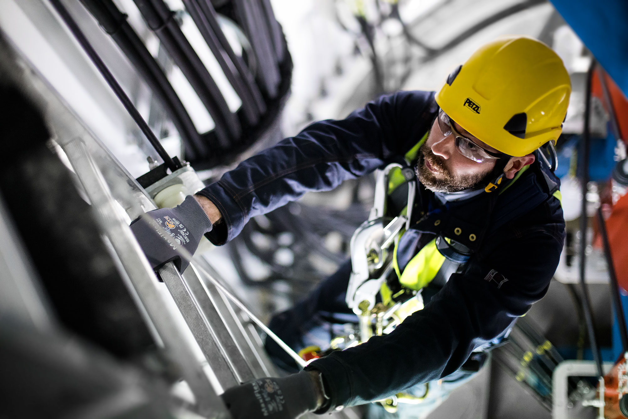 Technician climbs access ladder inside of a wind turbine |  Scott Gable industrial photographer