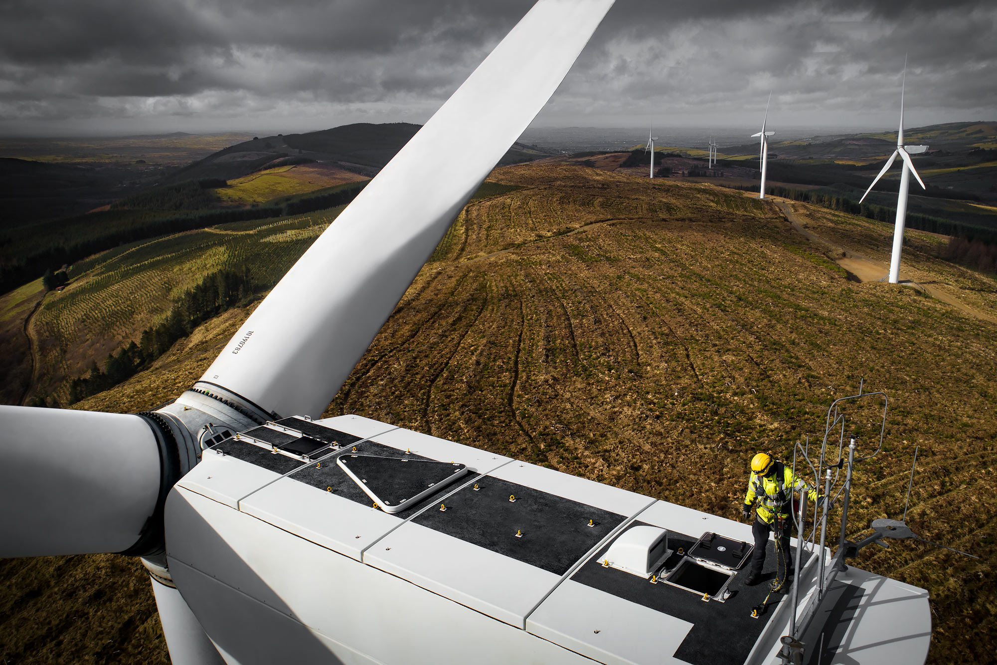 Aerial view of technician standing on top of a wind turbine |  Scott Gable industrial photographer
