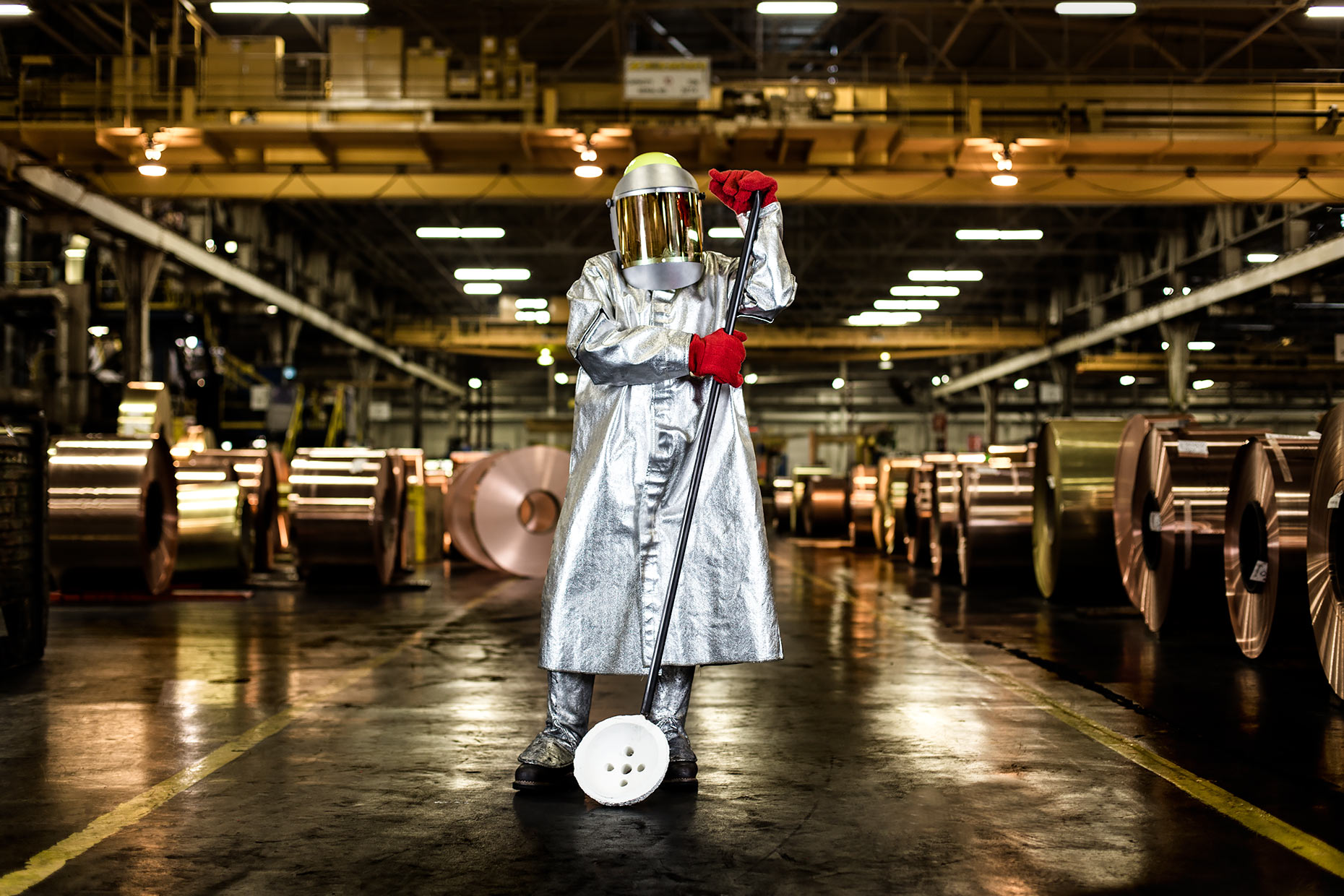A brass manufacturing technician in full safety gear standing among brass rolls  | Scott Gable industrial photographer