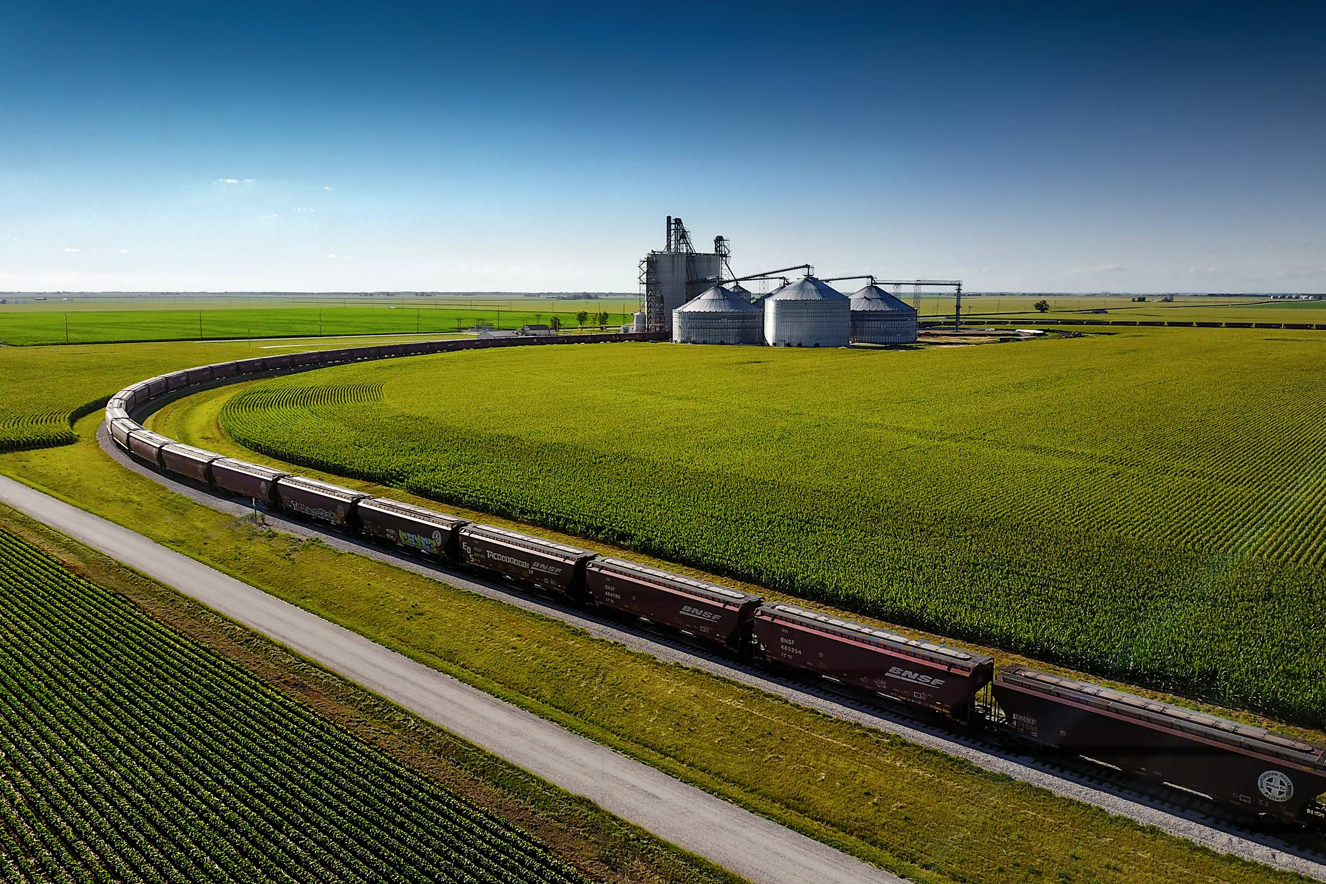 Freight train leaves grain silos through corn fields | Scott Gable industrial photographer
