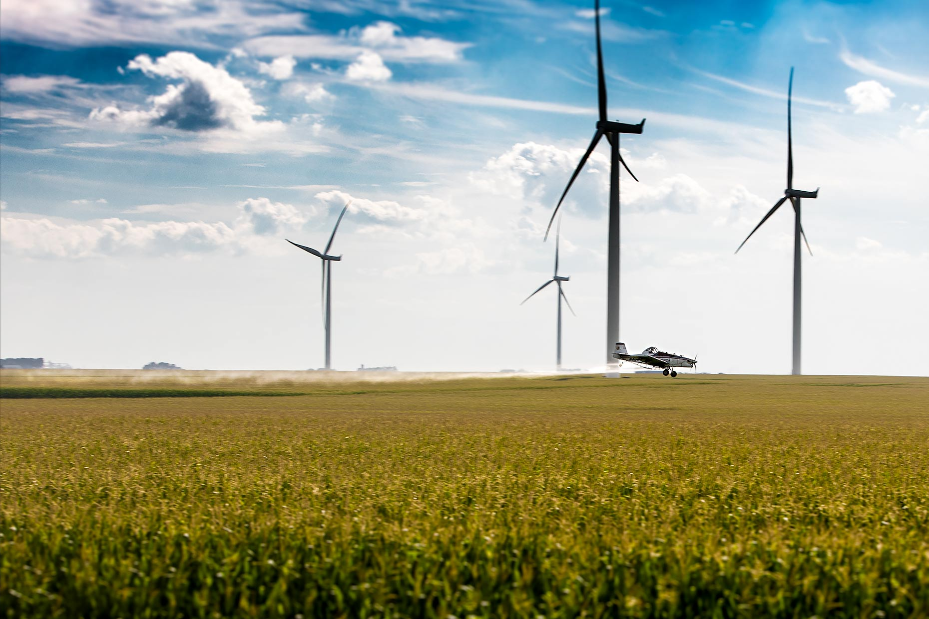 A crop duster flies over a corn field with wind turbines above | Scott Gable industrial photographer