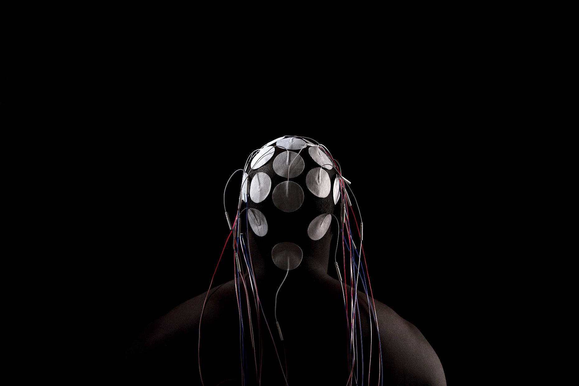 Electrodes on the back of the head of a bald, African American, male model with dark background | Scott Gable industrial photographer