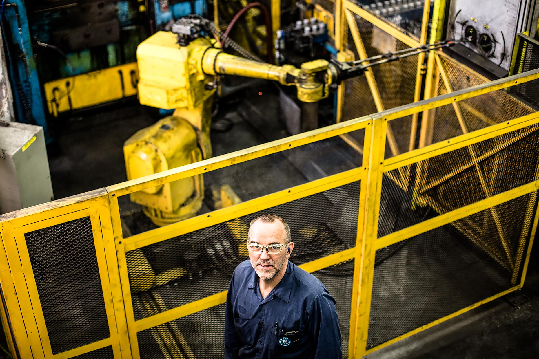 Technician poses in front of robot arm |  Scott Gable industrial photographer