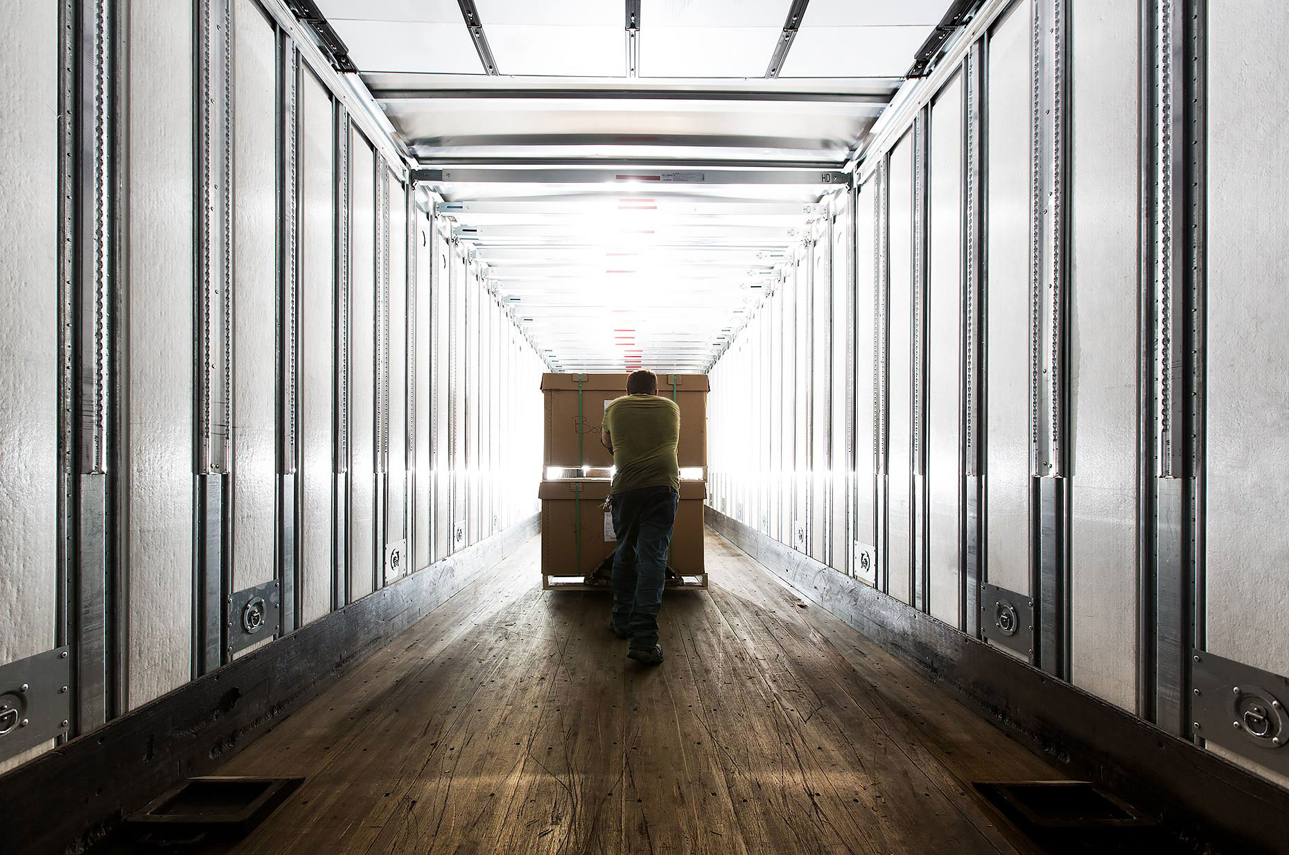 Warehouse worker pushes a load of boxes down a hallway |  Scott Gable industrial photographer