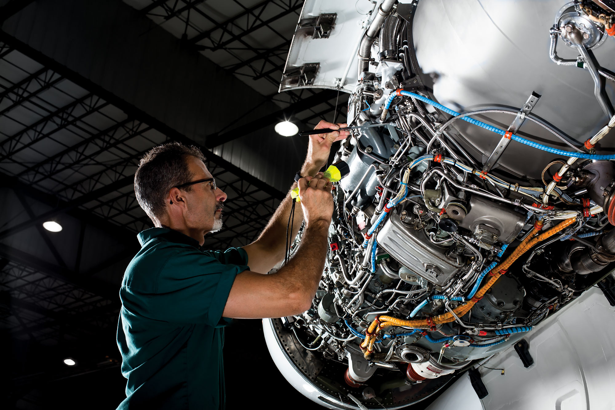 technician inspects jet engine cowling